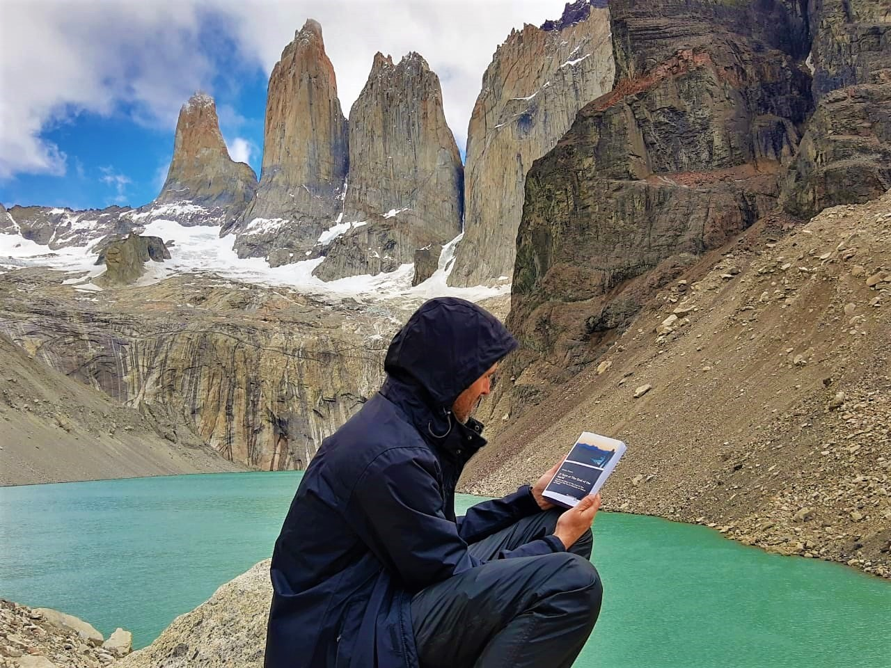 """A wonderful picture of the book """"21 Days at The End of The World"""" in Torres del Paine – Tierra del Fuego, Chile. In 2013 Torres del Paine was elected and considered the 8th wonder of the world. It is in this mystical place that the main character of the book meets Alnitak – the Guanacos protector, a character full of magic and mysteries. Photo by Mauro Molina (Brazil)."""