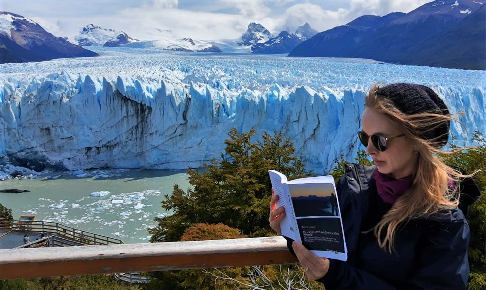 """Amazing picture of the book """"21 Days at The End of The World"""" in the Glacier National Park near the city of El Calafate – Patagonia Argentina, with Perito Moreno Glacier in the background. The photo was taken by photographer Mauro Molina during his trip to the far south of America, when he is getting to know some of the places that served as scenery for the book."""